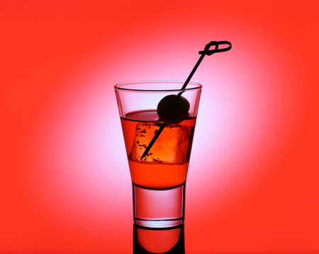shooter drink: drink glass with red liquid and green olive on red background