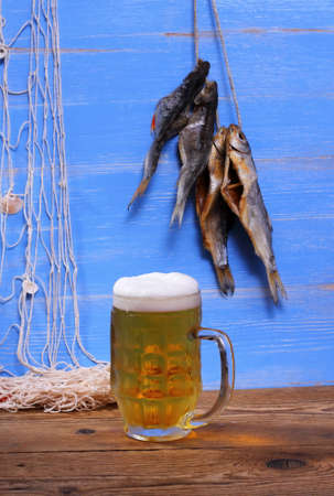 rudd: Mug of beer on blue background, dried rudd fish and fishing net Stock Photo