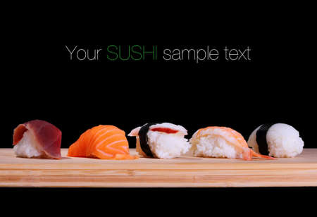 Five species of fish sushi on bamboo board, text space Imagens