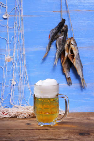 rudd: Beer on blue background, dried rudd fish and fishing net Stock Photo