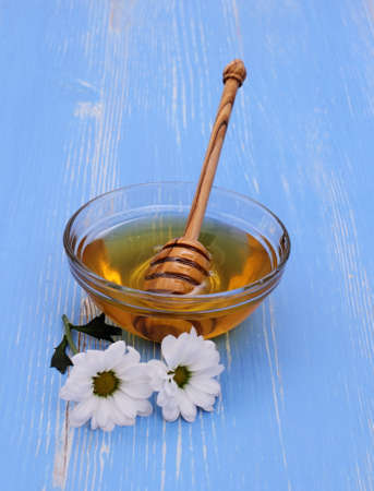 Honey bowl with dipper and blossom on blue wood table photo