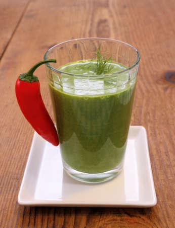 Green smoothie spinach and sweet red peppers, wooden background photo