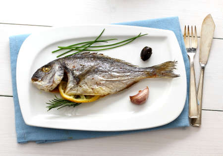 Garnished grilled whole sea bream with olives, top view photo