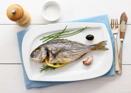 Garnished grilled whole sea bream with lemon, top view photo
