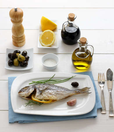 Garnished grilled sea bream with olives, lemon, top view photo