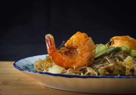 Asia Glass noodles with red prawn and vegetables dark background photo