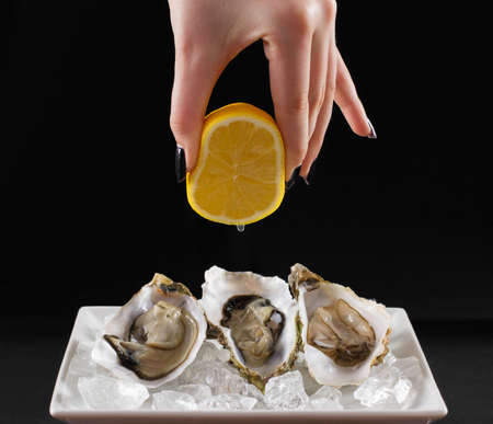 Womans hand squirt three oyster shell with lemon juice, dark background