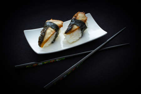 two on top: Two nigiri eel sushi with chopstick on black top view