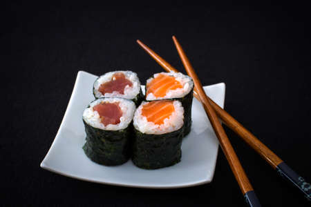 downloaded: Four salmon tuna maki sushi and chopstick on black close up Stock Photo