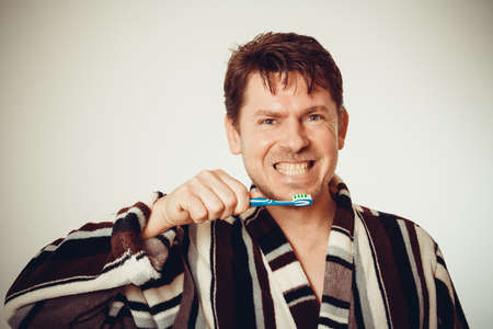 Good-humored man in bathrobe brushing teeth in vintage look photo