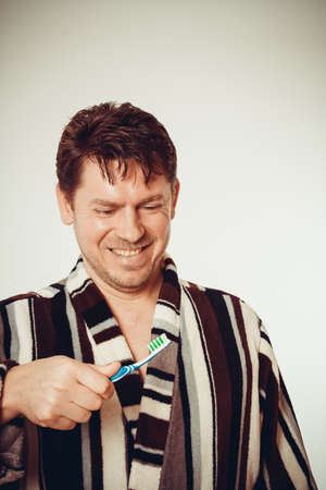 Laughing man in bathrobe brushing teeth in vintage look photo