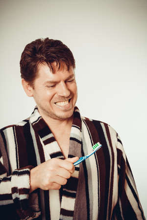 Young man in bathrobe brushing teeth in vintage look photo