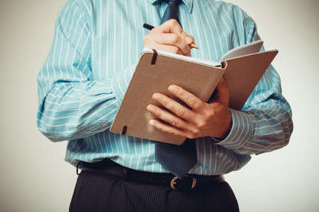 half body: Businessman is writing in notebook, half body, vignette style Stock Photo