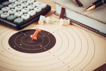 projectile: Red pin in target, pocket calculator, objectives and planning concept, close up Stock Photo