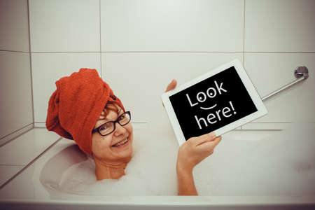 Happy woman in bathtub with tablet computers, close up photo
