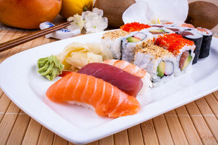 Appetizing sushi with wasabi, fruits and chopsticks closeup