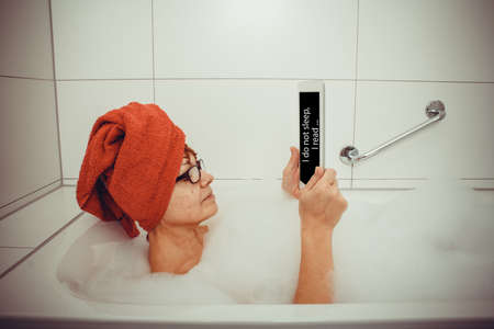 Woman in bathtub with tablet computers, space for text, retro style photo