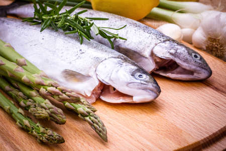 Raw trout with green asparagus, lemon and rosemary, close up photo