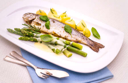 Grilled trout with green asparagus and rosemary potatoes, hollandaise sauce photo