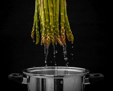 Green asparagus bundles with water flowing in metal pot, black background photo