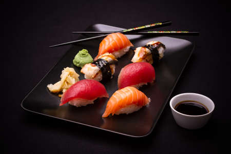 sushi restaurant: Eel Salmon and tuna sushi with chopsticks dark background Stock Photo