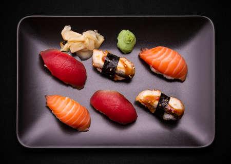 Tuna, salmon and eel sushi on black plate, top view