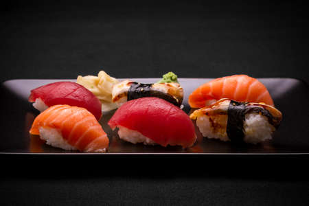 Tuna, salmon and eel sushi on dark background, close up