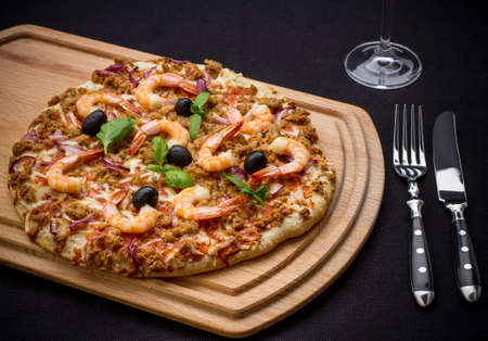 Tuna pizza with shrimp and black olives, top view
