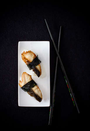 Two nigiri eel sushi with chopstick on black background, top view photo