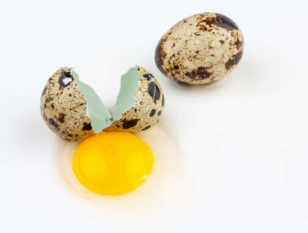 Two broken quail eggs on white background, top view