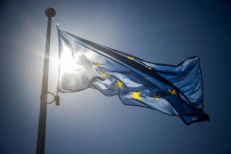 the european economic community: European Union flag on blue sky background, contre-jour backlighting