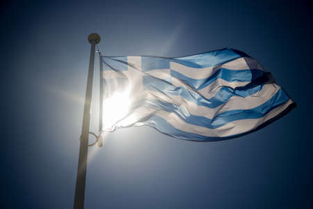 crisis: Greek flag waving before sun on blue sky, backlighting contre-jour