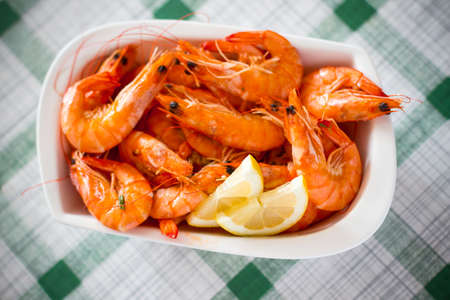 Fresh grilled shrimps with lemon close up, top view