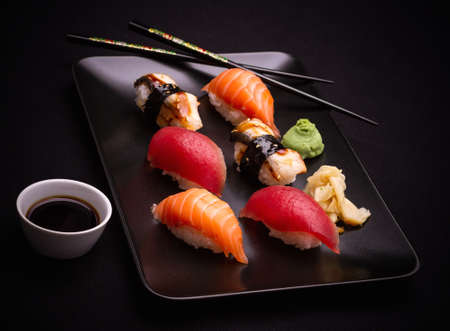 sushi restaurant: Salmon, tuna and eel sushi with chopsticks, dark background