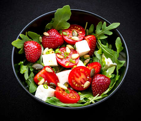 dinner plate: Strawberry tomato salad with feta cheese, olive oil on black, top view
