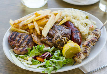 Mix meat plate with french fries, Greek food 写真素材