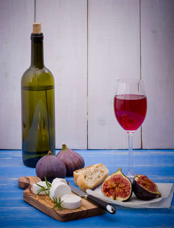 bootle: Goat cheese with ripe figs and wine on blue background