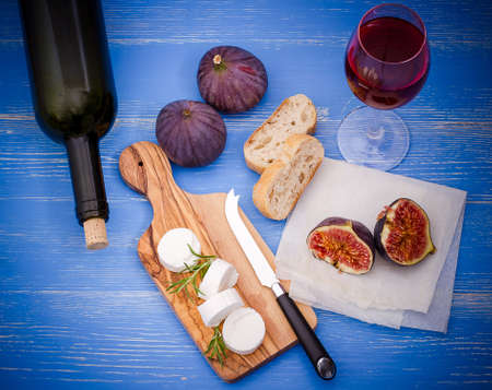 bootle: Feta cheese with ripe figs and wine on blue, top view