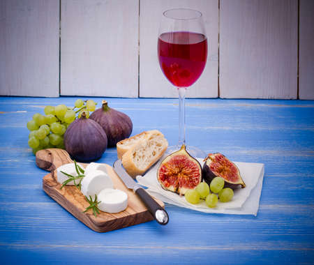 bootle: Feta cheese with ripe figs and wine on blue, horizontal Stock Photo