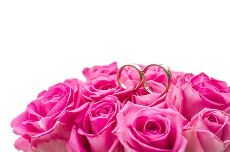 Two wedding rings on rose roses, top isolated