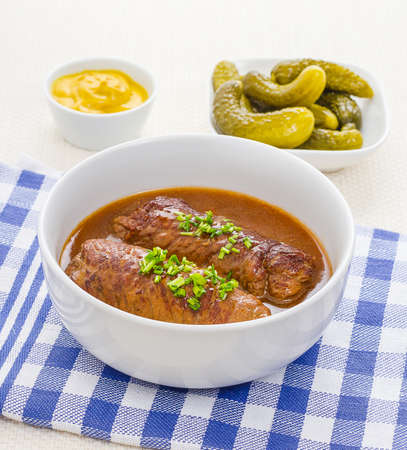 marinated gherkins: Two roulades beef in bowl with sauce, mustard gherkins