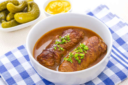 marinated gherkins: Two roulades beef in bowl with sauce, mustard and gherkins
