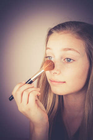 to conceal: Blond girl, makeup brush trying to conceal, grain effect, vintage, old fashion Stock Photo