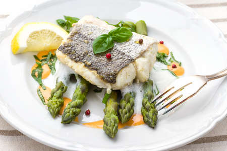 hake: Hake fillet with asparagus foam sauce and fork, top view