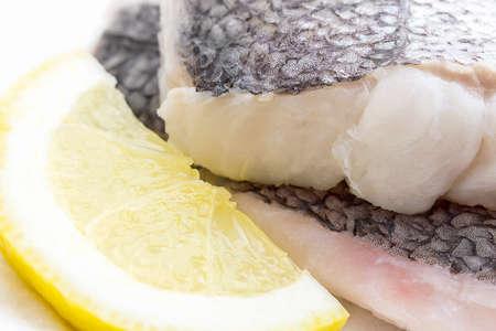 flesh eating animal: Hake fillet with skin and lemon, macro, as background, soft focus