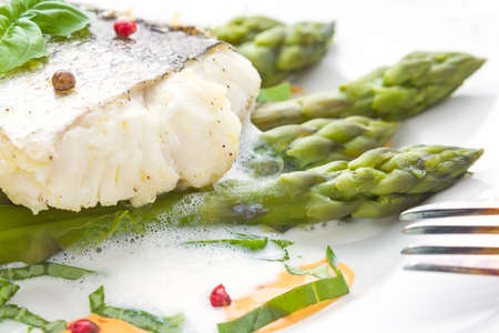 makro: Fish fillet with asparagus foam sauce and fork, makro, soft focus Stock Photo