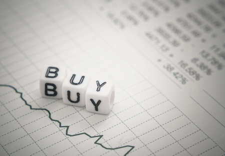 selective focus: Text buy from letters cube on chart stock report, top view, soft focus
