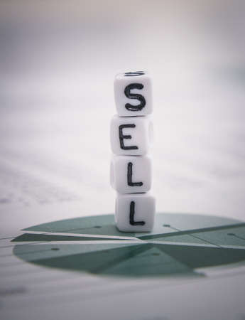 soft sell: Tower word sell from letters cube on diagram stock report, soft focus