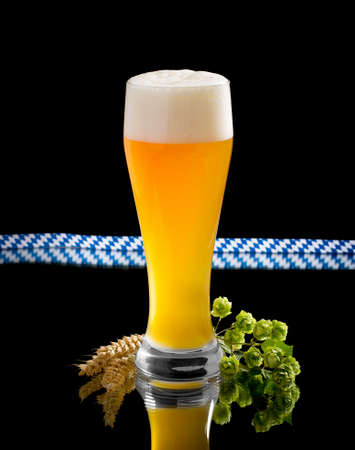 turbid: Natural turbid yeast wheat beer in glass with hop and wheat spike on black Stock Photo