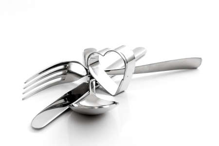 Cutlery, fork, spoon, with knife and heart isolated on white Stock Photo